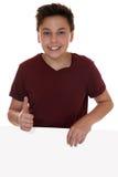 Lächelnder Junge mit einer leeren Fahne mit dem copyspace, das Th zeigt Stockfotografie