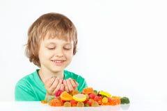 Lächelnder Junge mit farbigen Bonbons und Geleesüßigkeiten auf weißem Hintergrund lizenzfreies stockfoto