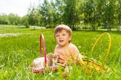 Lächelnder Junge mit Kaninchen und Körbe auf dem Gras Stockbilder