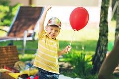 Lächelnder Junge mit rotem baloon Stockfotografie