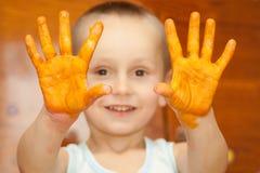 Lächelnder Junge mit seinen Händen stockfoto