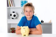 Lächelnder Junge mit Sparschwein Lizenzfreies Stockfoto