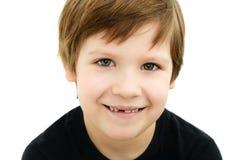 Lächelnder Junge ohne einen Milchzahn auf einem weißen Hintergrund lizenzfreie stockbilder