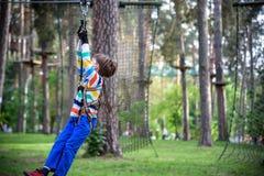 Lächelnder Junge reitet eine Ziplinie glückliches Kind auf der Ziplinie Das Kind verabschiedet den Seilhindernislauf stockbild