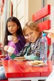 Lächelnder Junge und nettes Mädchen, die draußen im Café sitzen Stockbild