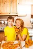 Lächelnder Junge und seine Mutter mit Pizzascheibe stockfotografie