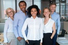 Lächelnder junger afrikanischer Führer, der Kamera mit verschiedenem Team betrachtet stockbild