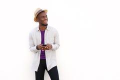 Lächelnder junger afrikanischer Mann mit einem Mobiltelefon Stockbild