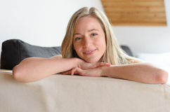 Lächelnder junger blonder Student, der auf Bett liegt Lizenzfreies Stockbild