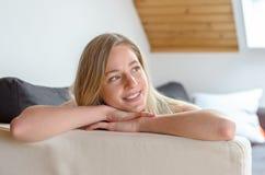 Lächelnder junger blonder Student, der auf Bett liegt Lizenzfreie Stockfotografie