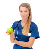 Lächelnder junger Doktor, der einen grünen Apfel gibt. Stockfotografie