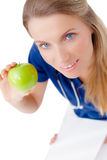 Lächelnder junger Doktor, der einen grünen Apfel gibt. Lizenzfreie Stockbilder