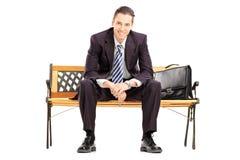 Lächelnder junger Geschäftsmann, der auf einer Holzbank sitzt Lizenzfreies Stockfoto