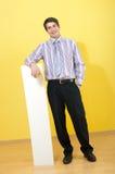 Lächelnder junger Geschäftsmann, der auf leerem Blatt sich lehnt lizenzfreie stockbilder