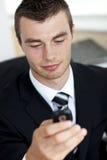 Lächelnder junger Geschäftsmann, der eine Meldung sendet lizenzfreie stockbilder