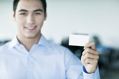 Lächelnder junger Geschäftsmann, der eine Visitenkarte und das Betrachten der Kamera hält Stockfotos