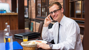 Lächelnder junger Geschäftsmann, der einen Anruf mit seinem Smartphone in einem Restaurant macht. Stockfotografie