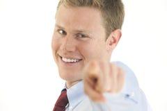 Lächelnder junger Geschäftsmann, der Finger auf camer zeigt Stockfotografie