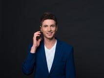 Lächelnder junger Geschäftsmann, der Gläser hält und am Handy über grauem Hintergrund spricht Stockfoto