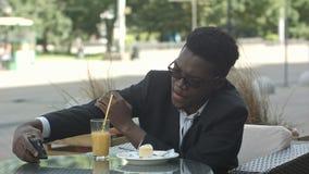 Lächelnder junger Geschäftsmann, der an der Kaffeestube unter Verwendung des Handys, selfie nehmend sitzt stock video