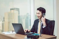 Lächelnder junger Geschäftsmann, der an Laptop arbeitet stockfotos