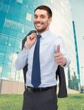 Lächelnder junger Geschäftsmann, der sich Daumen zeigt Stockfotos