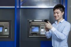 Lächelnder junger Geschäftsmann, der vor einem ATM und dem Betrachten seines Telefons steht Lizenzfreies Stockfoto