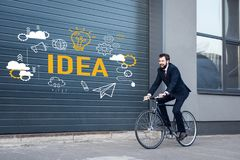 lächelnder junger Geschäftsmann im Klagenreiten fahren auf Straße mit Ideenaufschrift- und -geschäftsikonen rad
