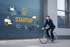 lächelnder junger Geschäftsmann im Klagenreiten fahren auf Straße mit Startaufschrift- und Geschäftsikonen rad