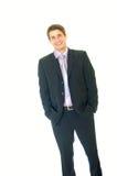 Lächelnder junger Geschäftsmann mit den Händen in den Taschen stockbild