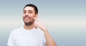 Lächelnder junger gutaussehender Mann, der auf Backe zeigt Lizenzfreie Stockbilder