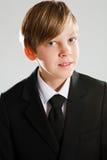 Lächelnder junger Junge, der schwarzen Anzug trägt Lizenzfreie Stockbilder