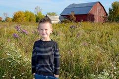 Lächelnder junger kaukasischer Junge auf dem ländlichen Gebiet Stockfotografie