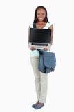 Lächelnder junger Kursteilnehmer, der ihren Laptop zeigt Stockbilder