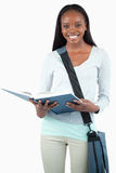 Lächelnder junger Kursteilnehmer mit Beutelmesswert in ihrem Buch Stockfotos
