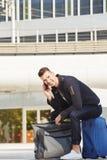 Lächelnder junger Mann auf dem TelefonAnklopfen mit Gepäck Stockbilder