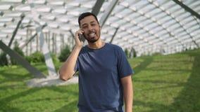 Lächelnder junger Mann, der auf Telefonstellung auf grünem Rasen spricht stock video