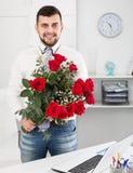Lächelnder junger Mann, der Blumenfrau darstellt Stockfotografie