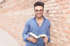 Lächelnder junger Mann, der ein Buch hält Lizenzfreies Stockbild