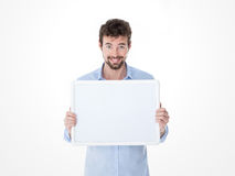 Lächelnder junger Mann, der ein leeres Brett hält Stockbilder