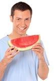 Lächelnder junger Mann, der eine Scheibe der Wassermelone zeigt Lizenzfreie Stockfotografie
