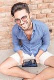 Lächelnder junger Mann, der an einem Tablet-Computer arbeitet Stockfoto