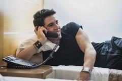Lächelnder junger Mann, der im Bett liegt und an spricht Stockfotografie
