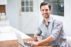 Lächelnder junger Mann, der Kaffeetasse mit Laptop hält Stockbild