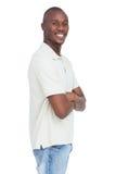 Lächelnder junger Mann, der mit den Armen gekreuzt steht Stockfotografie