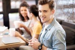 Lächelnder junger Mann, der sein Telefon verwendet lizenzfreie stockfotos