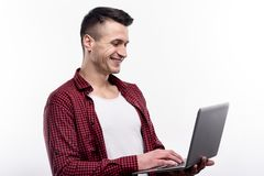 Lächelnder junger Mann, der seinen Laptop verwendet stockbilder