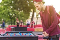 Lächelnder junger Mann, der Tabellenfußball foosball Außenseite hat Spaß mit Freunden d spielt lizenzfreies stockbild