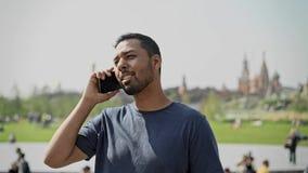 Lächelnder junger Mann, der am Telefon in Moskau am sonnigen Tag spricht stock footage