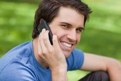 Lächelnder junger Mann, der am Telefon spricht Stockfotografie